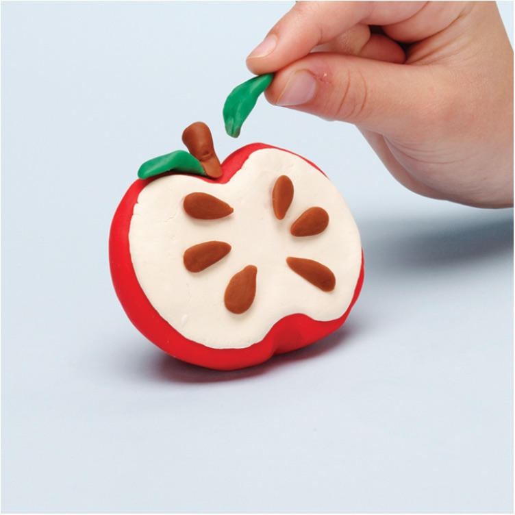 place pieces on the Play-Doh apple